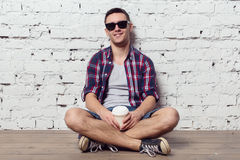 Young charming hipster sitting against the wall Stock Photos