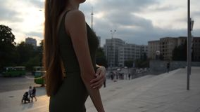 Young charming lady in slinky dress with body stands on the street in the evening stock video