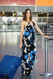 Young charming lady. Posing at the airport standing next to a suitcase dressed in a long dress royalty free stock photography