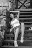 Young charming leggy girl with curly hair in a white shirt and red shorts sitting on the wooden stairs near the fortress in Lviv d Royalty Free Stock Images