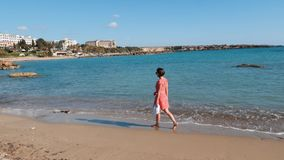 Young charming lonely girl walks along sandy beach near sea. Attractive caucasian woman in red dress walking on sea beach. Barefoo stock footage