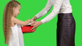 Young charming mother and her cute daughter opened christmas gifts on a green screen, chroma key stock video footage