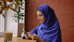 Young charming muslim woman in hijab rewrite info from card to her phone and smiling, sitting in cafe, beautiful female. With pierced nose stock video