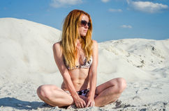 Young charming sexy girl with glasses, in a bathing suit with long hair sunning on the beach sand on the beach, hot, sunny day wit Royalty Free Stock Photography