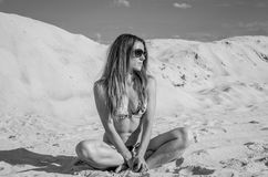 Young charming sexy girl with glasses, in a bathing suit with long hair sunning on the beach sand on the beach, hot, sunny day wit Royalty Free Stock Image