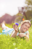 Young Charming Smiling Light-Haired Woman Lies on Green Grass in Royalty Free Stock Images