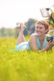 Young Charming Smiling Light-Haired Woman Lies on Green Grass in Stock Images