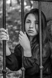 Young charming teenager girl with long dark hair sitting behind bars in a prison in the old castle fortress serving a sentence for. A crime with sad emotions Stock Photos