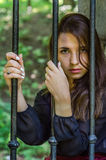 Young charming teenager girl with long dark hair sitting behind bars in a prison in the old castle fortress serving a sentence for. A crime with sad emotions stock images
