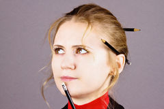 Young charming thoughtful woman with pencils. On a gray background Royalty Free Stock Photography