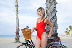 Young charming woman in bikini resting after ride on her retro bicycle along the beach Stock Images