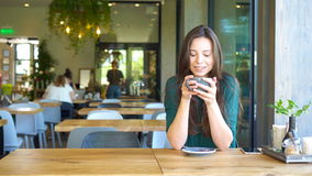 Young woman calling with cell telephone while sitting alone in coffee shop during free time. Attractive female with cute. Young charming woman calling with cell stock footage