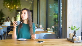 Young woman calling with cell telephone while sitting alone in coffee shop during free time. Attractive female with cute. Young charming woman calling with cell stock video footage