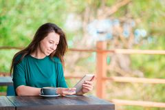 Young woman with smart phone while sitting alone in coffee shop during free time Stock Photo