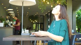 Young woman calling with cell telephone while sitting alone in coffee shop during free time. Attractive female with cute. Young charming woman calling with cell stock video