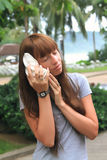 Young charming woman listening seashell Stock Photography