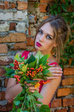Young charming woman with long blond hair with a professional make-up is the ruins of a brick wall with branches of wild grapes on Royalty Free Stock Image