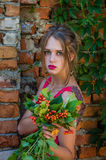 Young charming woman with long blond hair with a professional make-up is the ruins of a brick wall with branches of wild grapes on Royalty Free Stock Photo