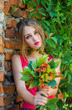 Young charming woman with long blond hair with a professional make-up is the ruins of a brick wall with branches of wild grapes on Stock Photography