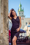 Young charming woman with long curly hair, strolling among the old town of Lviv architecture in sexy black dress Royalty Free Stock Image