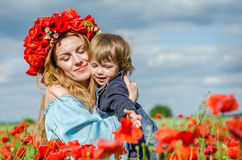 Young charming woman with long hair mom with her daughter in her arms walking in poppy field with a bouquet of poppies wreath on h Stock Images