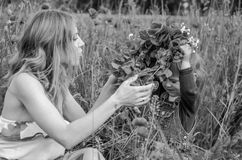Young charming woman with long hair mom with her daughter walking on the field among the grass, wove a wreath, a bouquet of red po Royalty Free Stock Photo