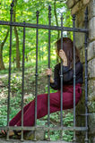 Young charming woman with long hair offender, sits behind bars in an ancient stone castle fortress prison prisoner and looks pityi Royalty Free Stock Image