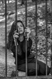 Young charming woman with long hair offender, sits behind bars in the old stone jail prisoner and looks pityingly through steel ba Royalty Free Stock Image