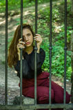 Young charming woman with long hair offender, sits behind bars in the old stone jail prisoner and looks pityingly through steel ba Stock Image