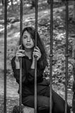 Young charming woman with long hair offender, sits behind bars in the old stone jail prisoner and looks pityingly through steel ba Royalty Free Stock Photography
