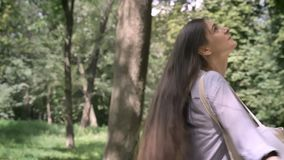 Young charming woman with long hair walking in park and turning around, holding bag, sunny beautiful day outdoors.  stock footage
