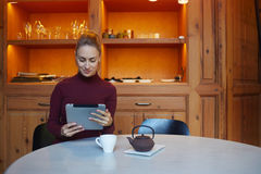 Young charming woman reading electronic book on digital tablet while relaxing in coffee shop after work day, Stock Image