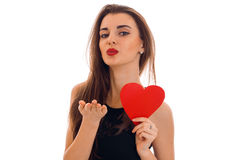 Young charming woman with red lips preparing to celebrate valentines day with heart symbol in studio isolated on white Stock Photo