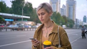 Young charming woman with short pink haircut holding coffee and phone, waiting for bus or taxi, standing on urban street