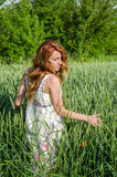 Young charming woman walking outdoors in a field near the green bushes and trees, hand patting wheat ears, dressed in a beautiful Stock Photo