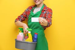 Young charwoman with business card. And cleaning supplies on color background stock image