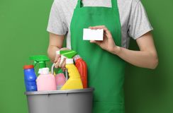 Young charwoman with business card. And cleaning supplies on color background royalty free stock images