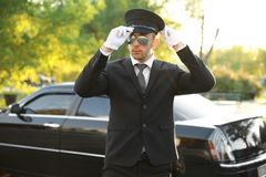 Young chauffeur adjusting hat near luxury car. On the street Royalty Free Stock Images