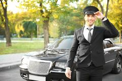 Young chauffeur adjusting hat near luxury car. On the street Stock Images