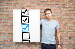 Young with checkboxes on whiteboard Stock Photography