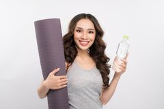 Young cheerful asian woman holding a bottle with water and yoga. Mat Stock Image