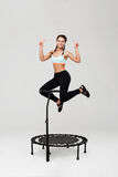 Young cheerful athlete jumping on rebounder smiling isolated on grey Stock Images