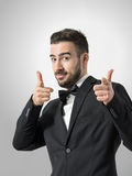 Young cheerful bearded man pointing finger gun gesture at camera. Stock Photography