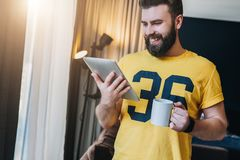 Cheerful bearded man stands and using tablet computer. Guy laughs looking screen of digital tablet while drinking coffee. Young cheerful bearded man stands in Stock Photography