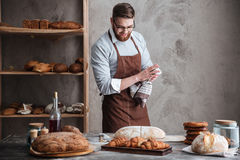 Young cheerful bearded man wearing glasses baker Stock Photos