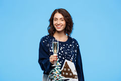 Young cheerful beautiful brunette girl in cosy knited sweater smiling holding glass of champagne over blue background. Stock Photo