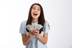 Young cheerful beautiful business girl holding money smiling in camera over white background Stock Photo