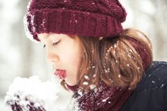 Young cheerful beautiful girl tasting soft new white snow. In her arms. Bright outdoors horizontal image with vintage filter Stock Photography