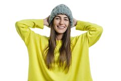 Young cheerful beautiful woman in yellow sweater and gray big loop knitted beanie hat looking at the camera on white isolated stock images