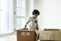 Young cheerful black boy moving to new house Stock Photo